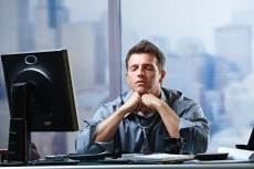 man in office with computer eyes closed