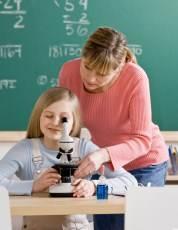 meisje kijkt  door microscoop met docent