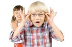 niño con gafas y niña detrás
