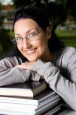 girl wearing glasses leaning on books